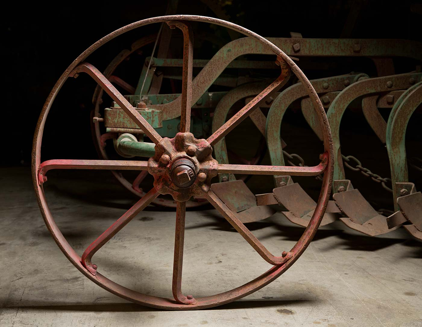 A red painted iron wheel, part of the stump-jump plough. - click to view larger image