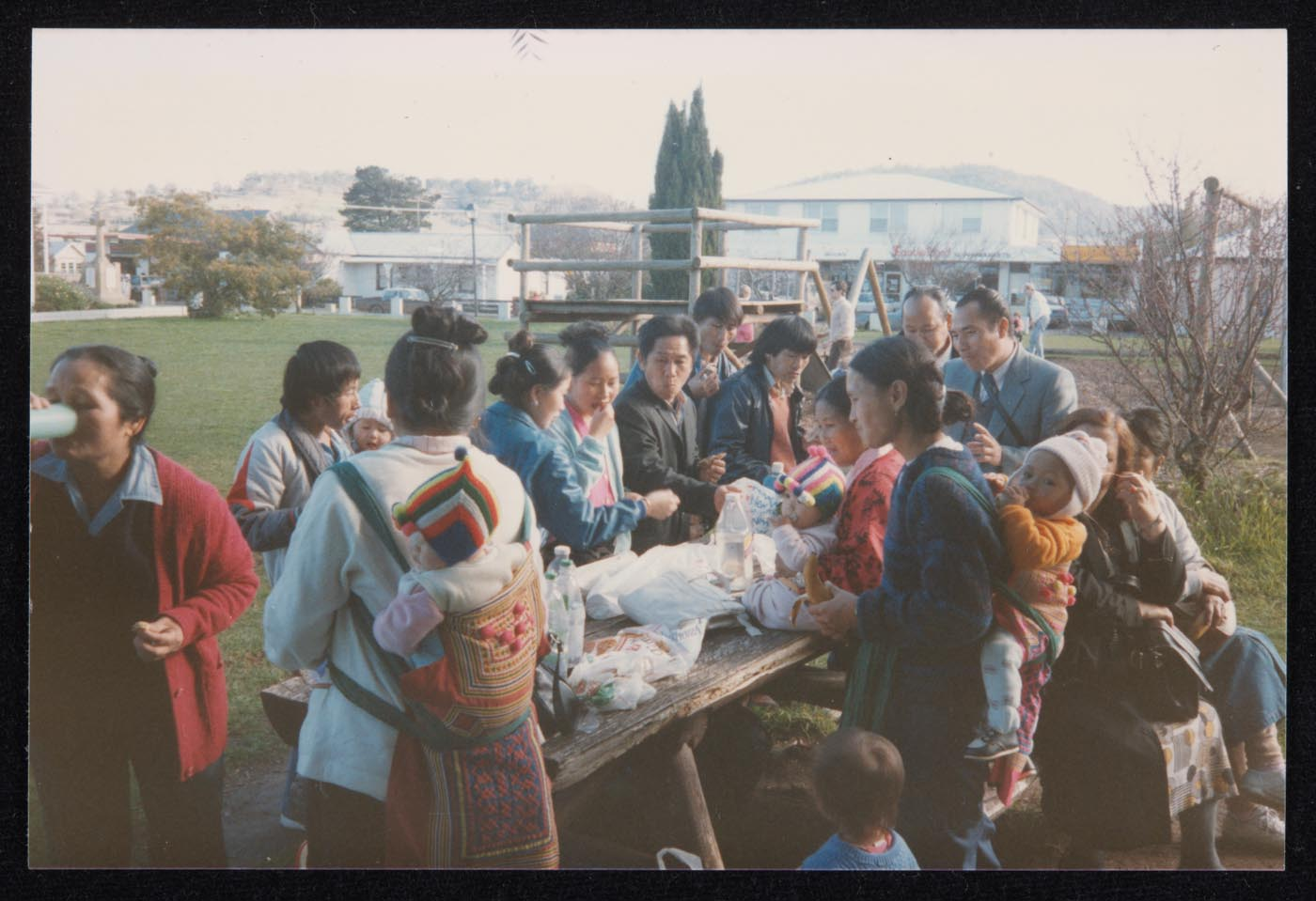 Colour photo of a group of people gathered in a park. They are sharing food which is laid out on a picnic bench.
