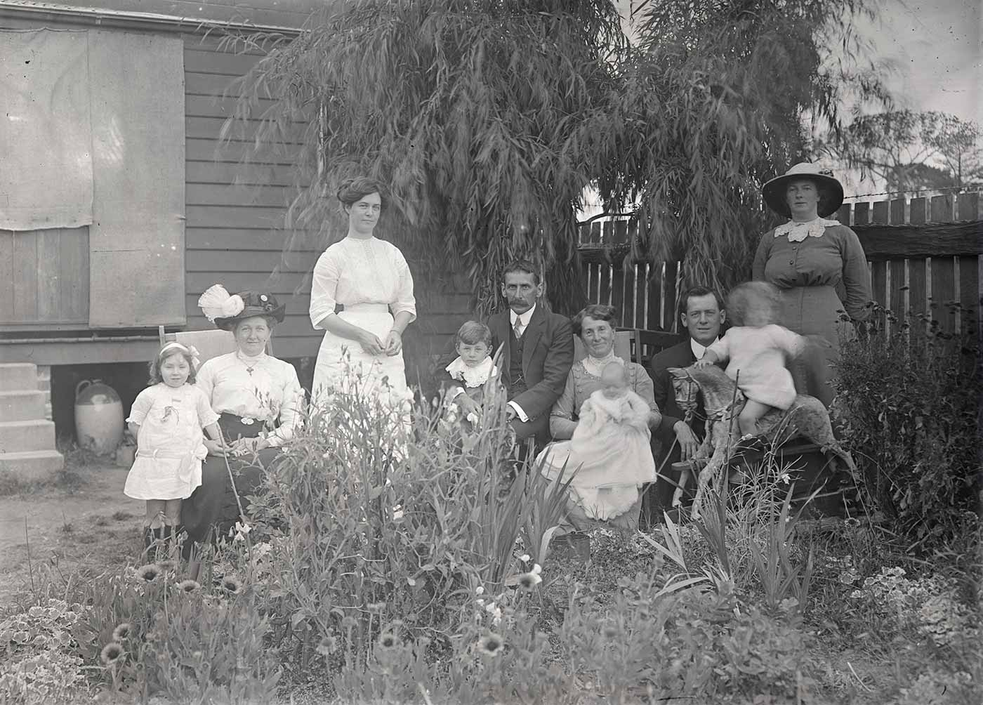 A photographic glass plate negative showing a group portrait of men, women, and children in a front garden. The group comprises of four woman, two men, and four children all in various poses. Two toy rocking horses are being played with by the children, and a section of a house is visible in the background. - click to view larger image