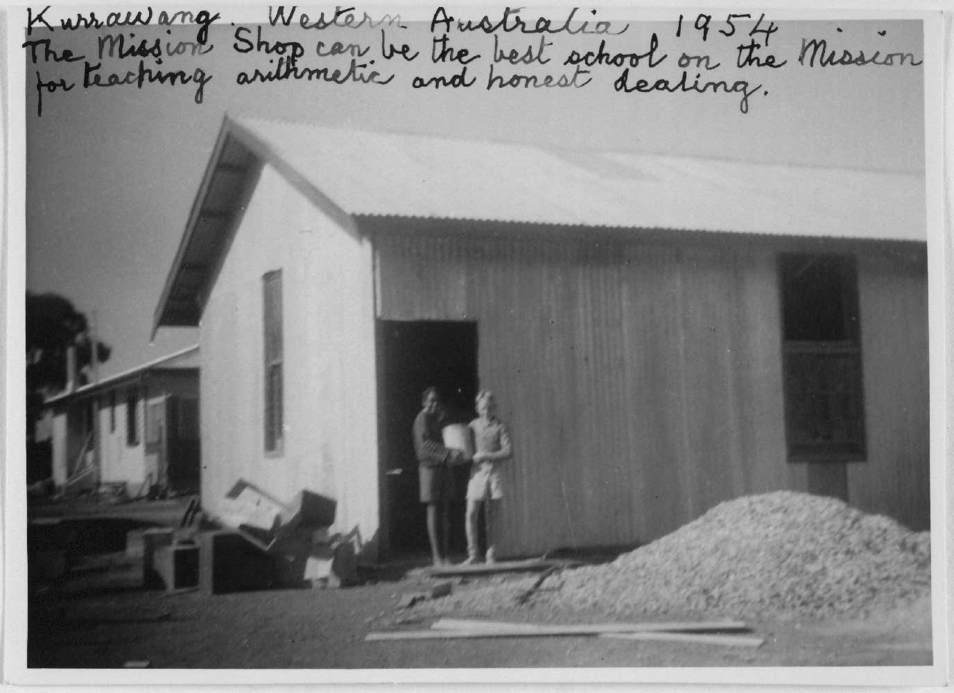 Black and white photo of a blurred image of two children. They are standing in front of a corrugated building surrounded by debris and a pile of gravel or stone like substance.