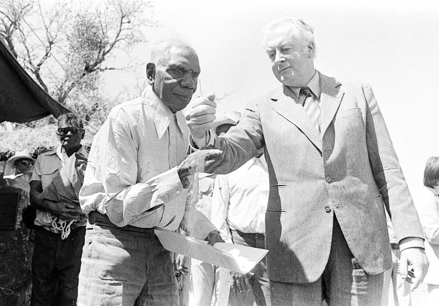 Black and white photo of Gough Whitlam pouring sand into Vincent Lingiari's hand in front of spectators.