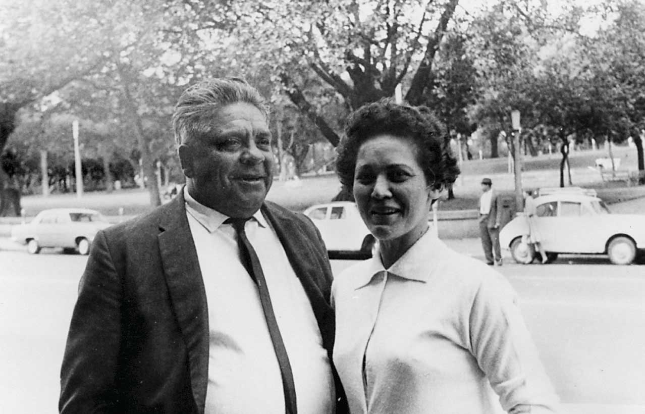 Black and white photo of a man and woman standing in business attire and standing on a street with a city park in the background.