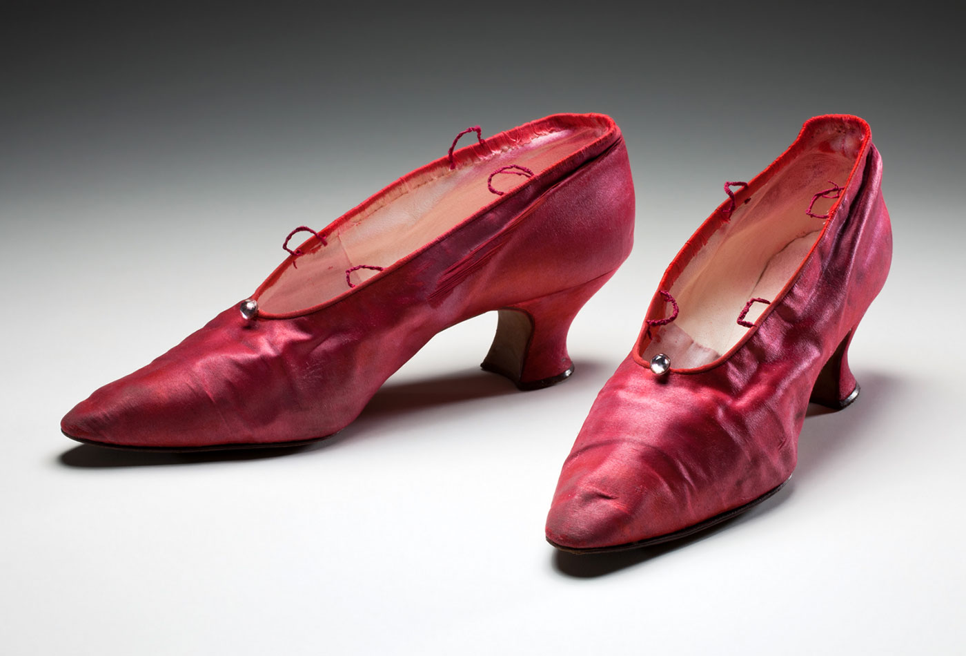 A pair of pink-dyed satin shoes, with a clear bead at cenre top, a Louis heel, narrow pointed toe and two thread loops on each side of the foot opening, for ankle ties.