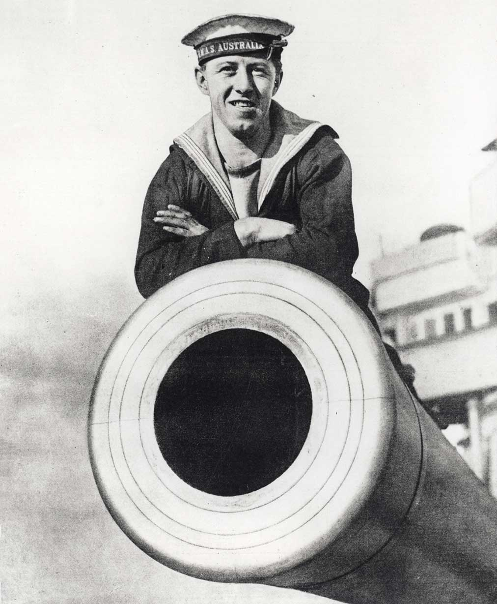 Black and white photograph of a sailor sitting atop a large gun barrel.