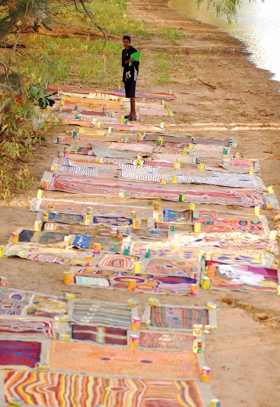 Co-curator Hayley Atkins at Nyarna (Lake Stretch) with paintings created along the stock route. - click to view larger image