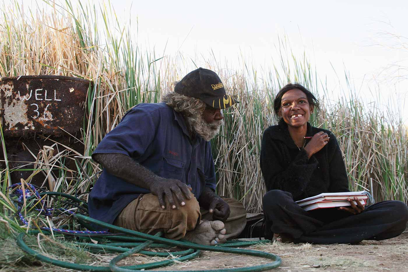 Colour photo of a man and woman sitting on the ground in discussion over plans.