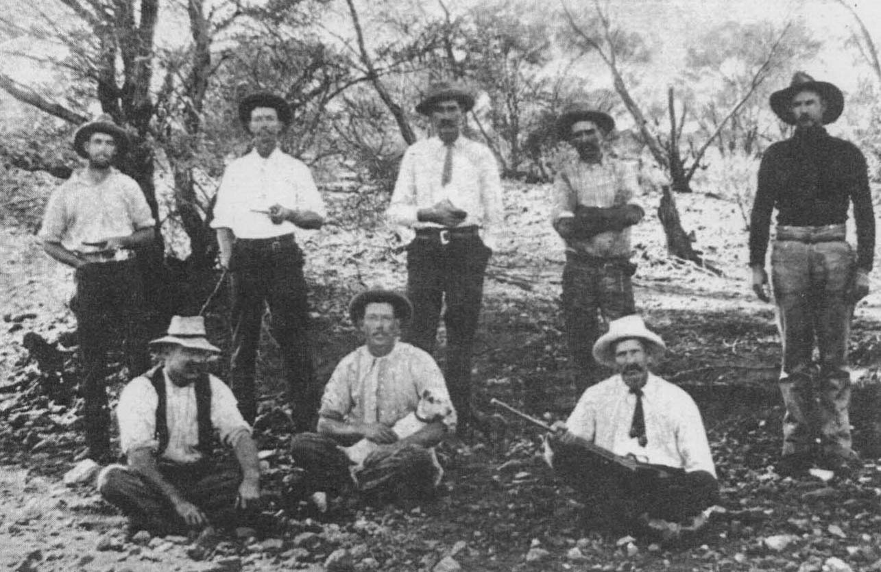 Black and white photo of eight men and a dog posing for a group photo in bushland.