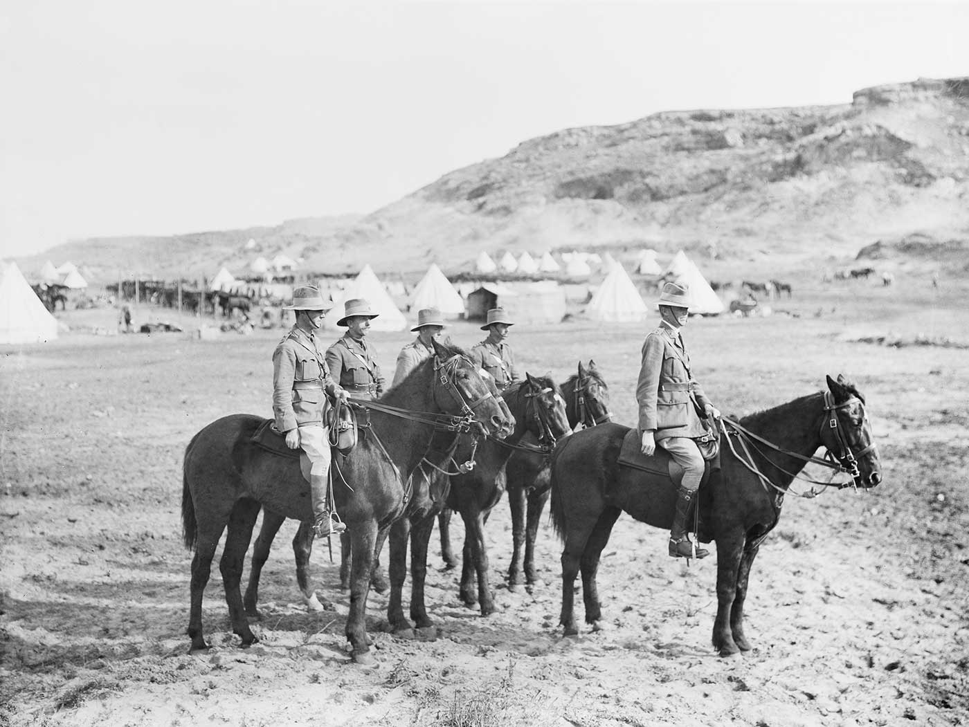Black and white photograph showing five men in military uniforms atop horses. Behind them are rows of tents and a line of horses in a desert landscape. - click to view larger image