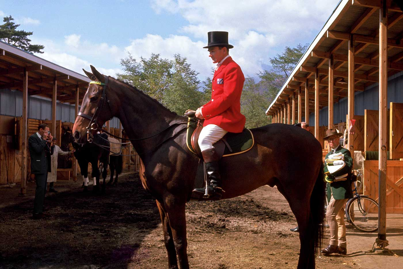 Side view of a a man wearing a red, tailored waistcoast, light jodphurs and a black hat, atop a horse with a plaited mane. - click to view larger image