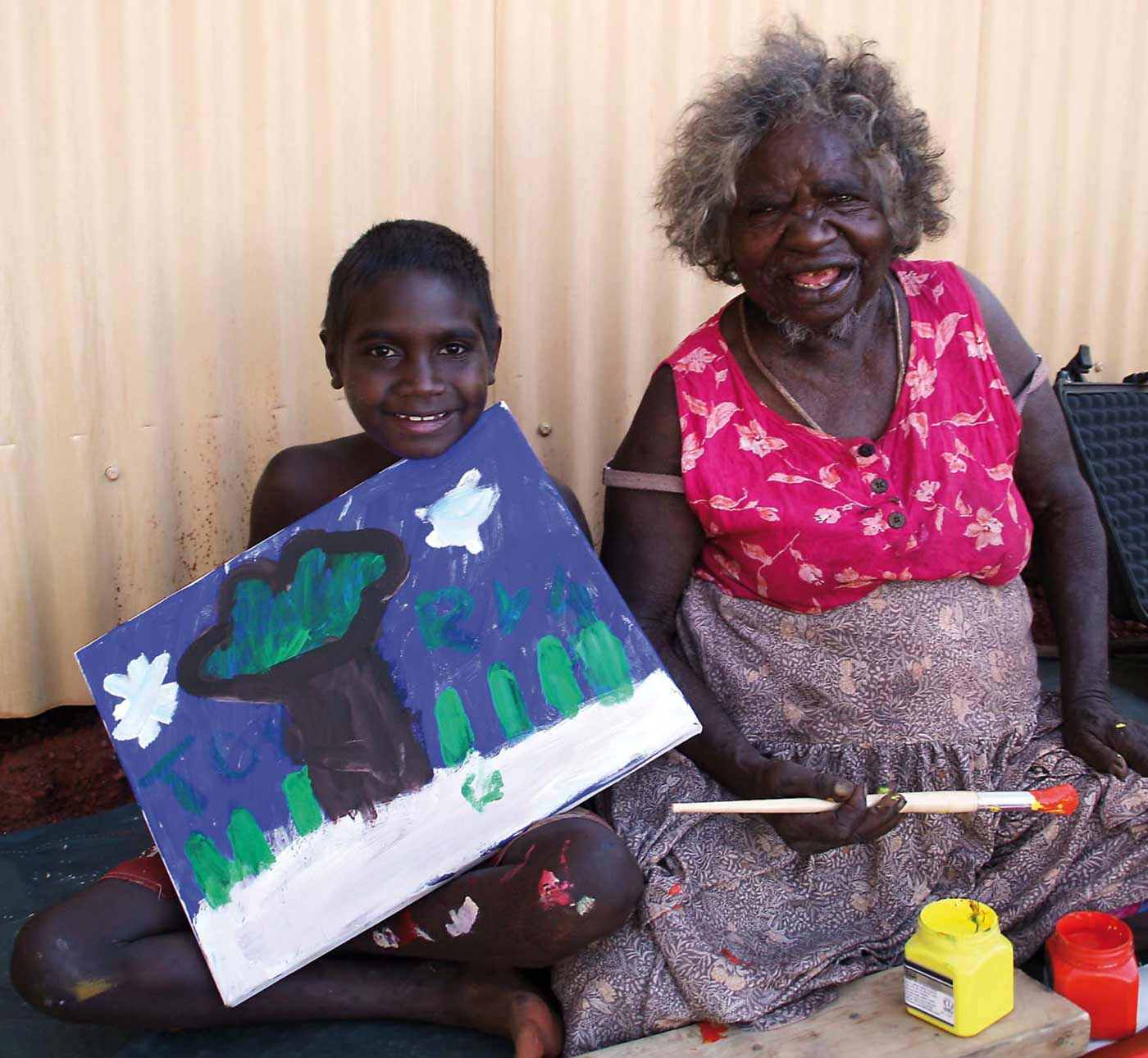 Colour photograph of an elderly woman sitting next to a young boy who is holding a painting. - click to view larger image
