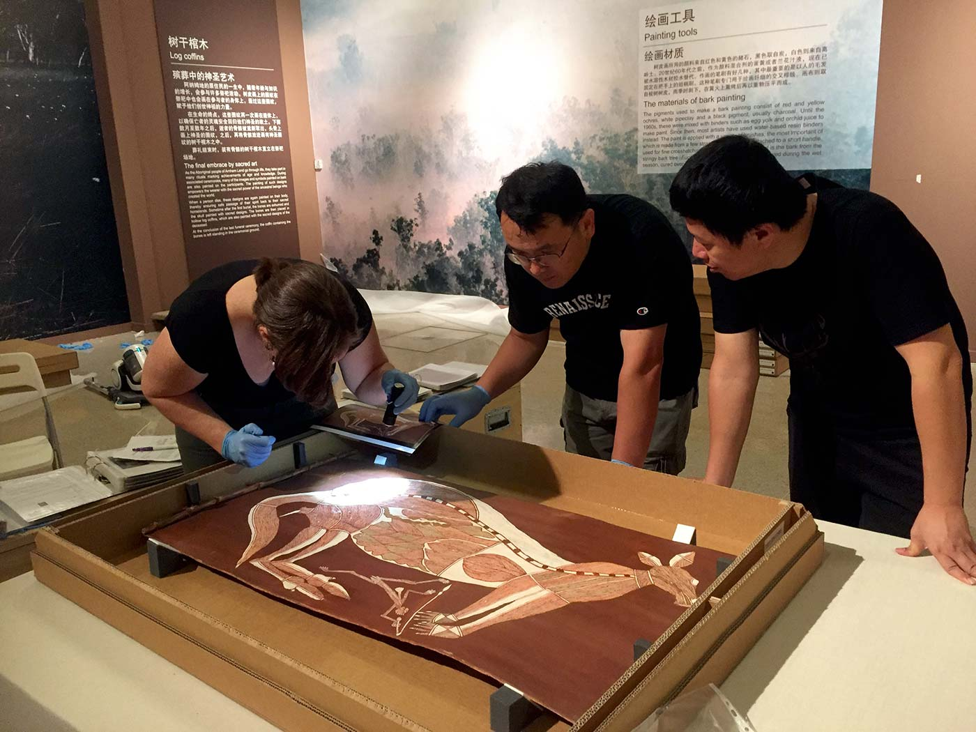 Three museum staff inspect an artwork featuring a kangaroo.