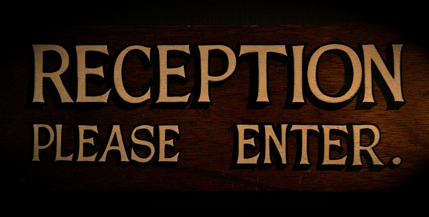 Colour photograph of a varnished timber sign, with gold text handpainted on a dark background. The text reads 'RECEPTION PLEASE ENTER'. - click to view larger image