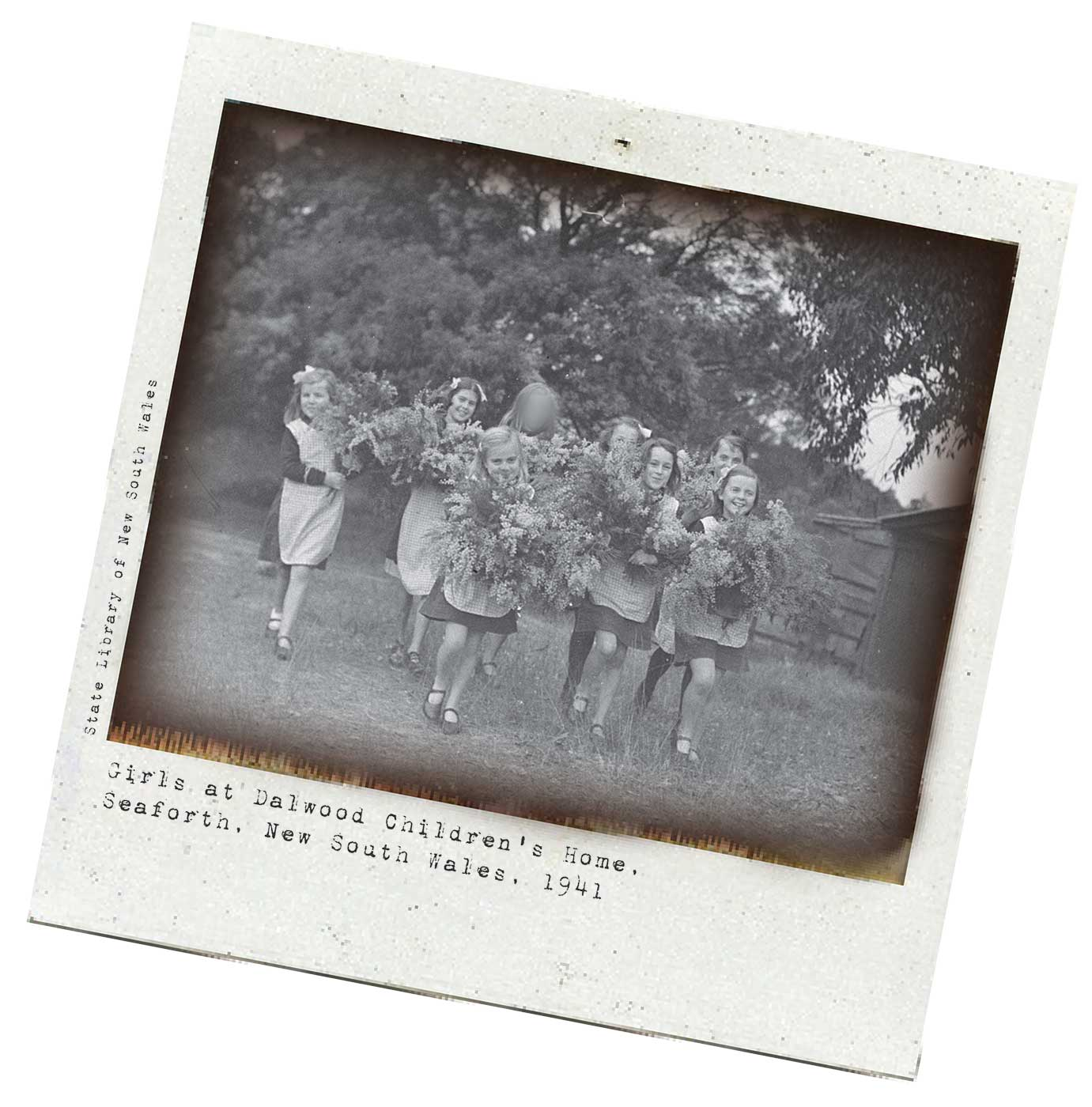 A black and white Polaroid photograph of several young girls carrying large sprays of flowers. The photograph has been taken outside with tall bushes and a building visible in the background.  The girls are walking towards the camera and are smiling. They are dressed alike in long-sleeved above knee dresses covered by lighter coloured checked aprons, the same style shoes, and ribbons in their hair.  Typewritten text underneath reads: 'Girls at Dalwood Children's Home. Seaforth. New South Wales, 1941'. Smaller text, on the left-hand side of the image, in a vertical direction, reads: 'State Library of New South Wales'. - click to view larger image