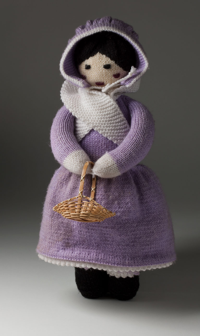 A colour photograph of a knitted doll wearing a purple dress, a purple bonnet and a white scarf. The doll is holding a small cane basket. - click to view larger image