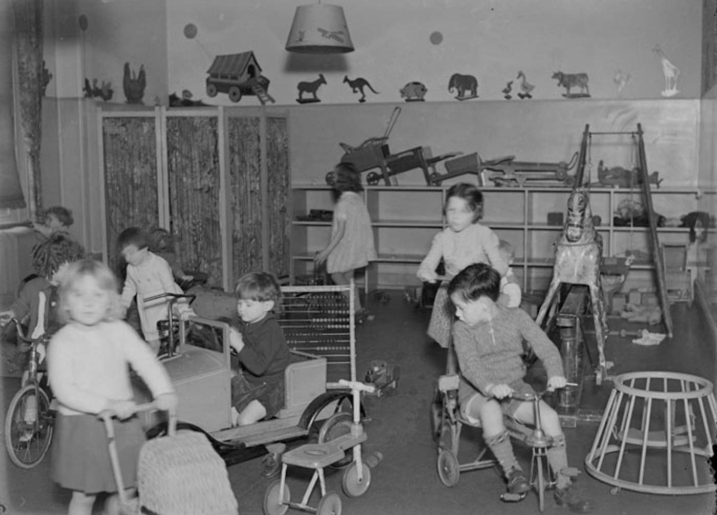 Eight small children in a room filled with toys. A girl in the foreground pushes a toy pram and several children ride trikes. Another girl sits in a toy car. The room includes an abacus, rocking horse and swing, with other toys stacked on shelves behind. - click to view larger image