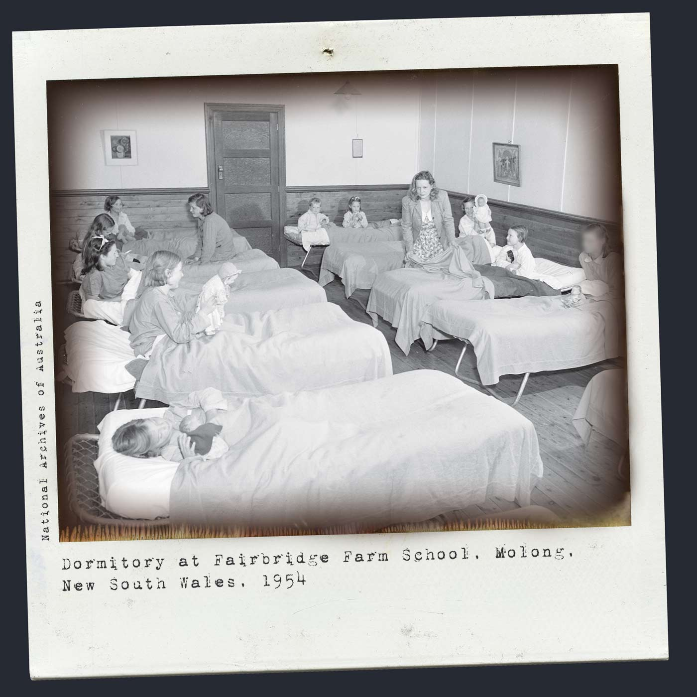 Polaroid photograph showing a group of young girls sitting in two rows of single beds, each holding a doll. An older woman and girl help the younger girls prepare for bed. Typed text below reads 'Dormitory at Fairbridge Farm School, Molong, New South Wales, 1954. National Archives of Australia'. - click to view larger image