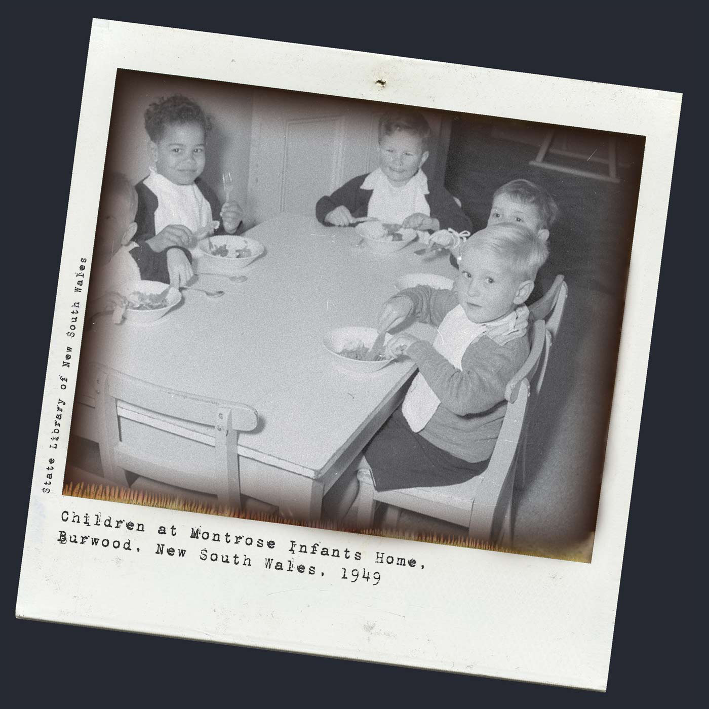 Black and white Polaroid photo showing five toddlers sitting at a small, wooden rectangular table. Each of the children wears a white bib and eats from a small bowl. Another child sits in a high chair, visible through a doorway at the far end of the shot. Typeritten text under the photo reads: 'Children at Montrose Infants Home, Burwood, 1949', and along the left side reads 'State Library of New South Wales'. - click to view larger image