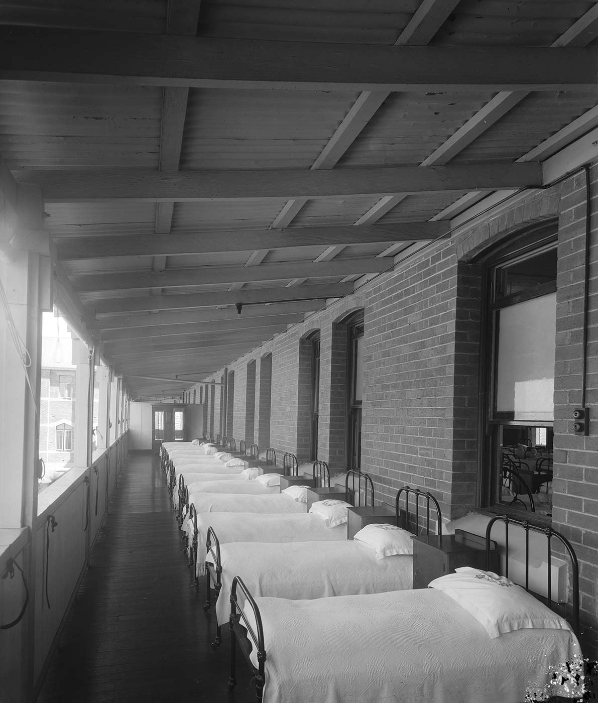 Black and white photo showing a row of single metal beds lined up against a brick wall. A timber wall with open windows is opposite and roof is made of corrugated iron. The beds have white bedspreads and pillow cases, with dressers in between each. - click to view larger image