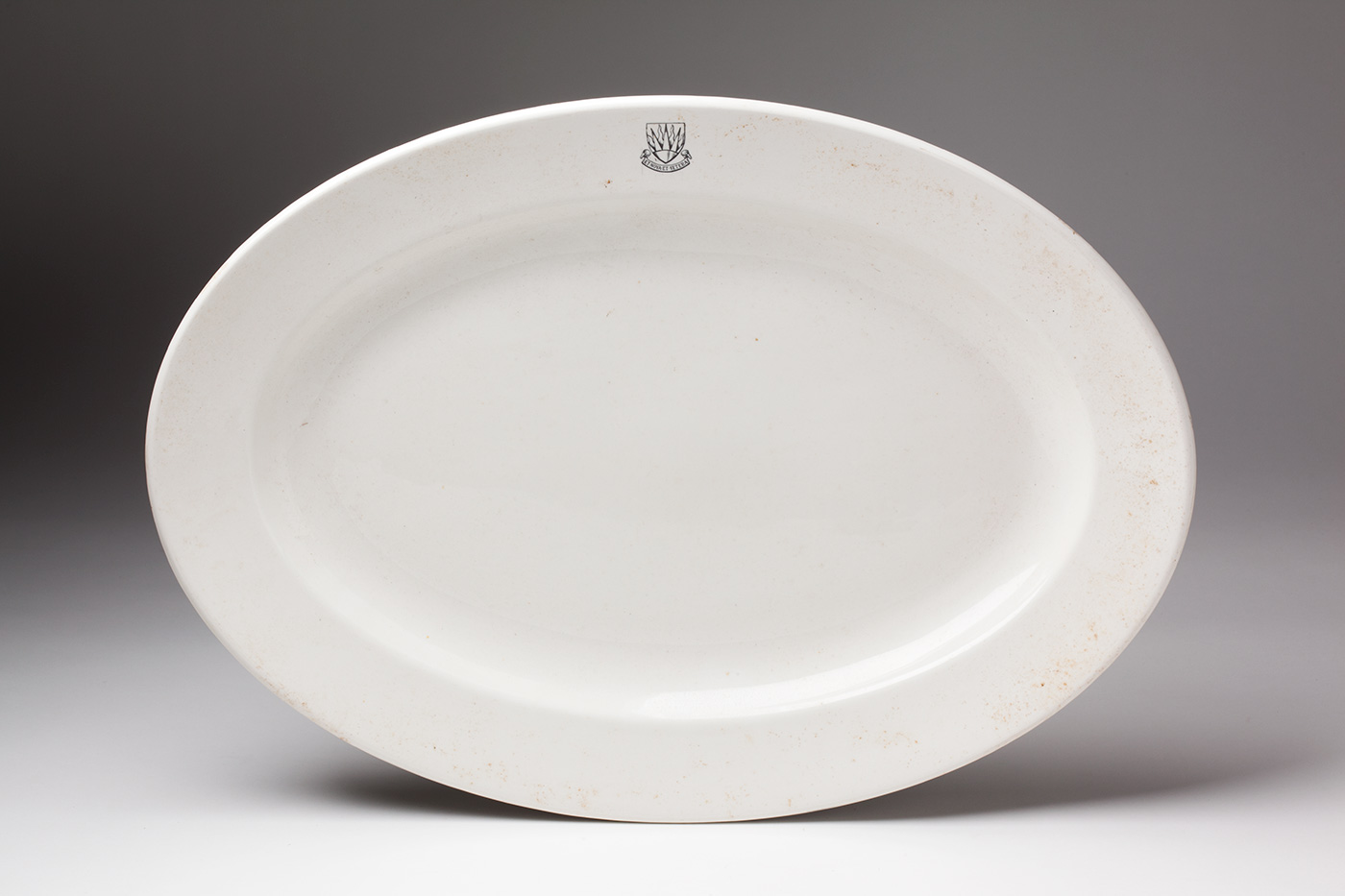A white oval ceramic platter with an emblem on the rim that includes the text 'ET NOVA ET VETERA'. - click to view larger image