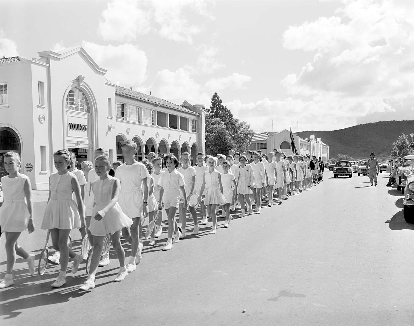 Black and white photo showing a group of children, wearing tennis whites and carrying racquets, marching along a street, three abreast. A white building with 'YOUNGS' on the facade is to the left of the marchers. A row of cars is partially visible on the right. - click to view larger image