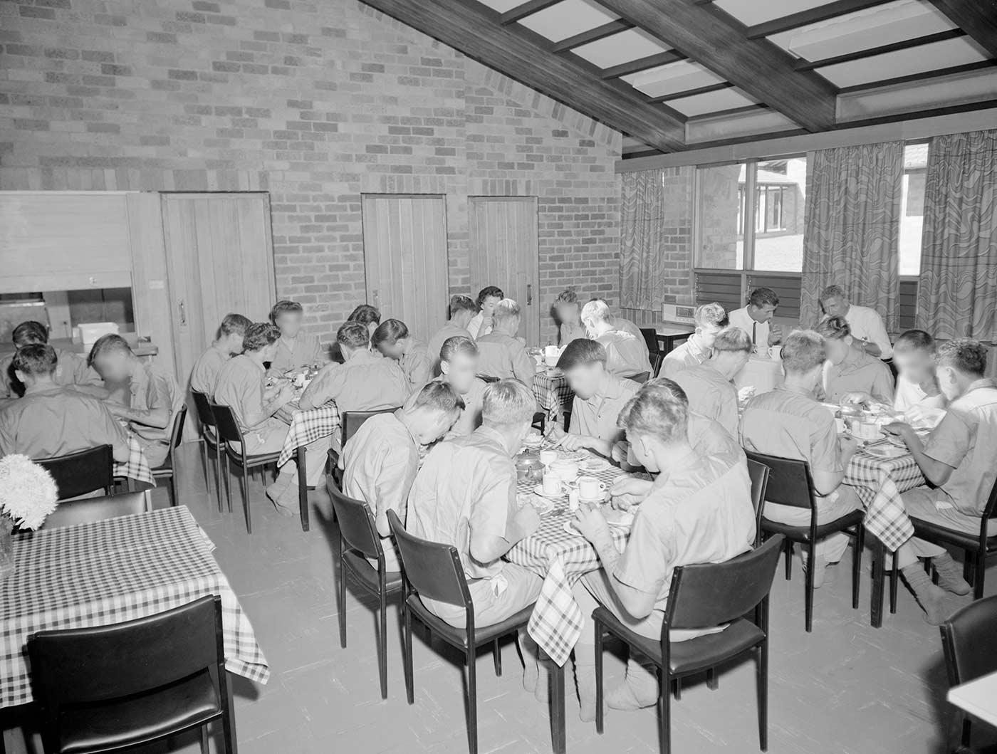 Black and white photo showing groups of teenage boys seated at dining tables. The tables are covered with checked tablecloths. The boys wear a uniform of short-sleeved shirts and shorts. They wear socks, but no shoes. - click to view larger image