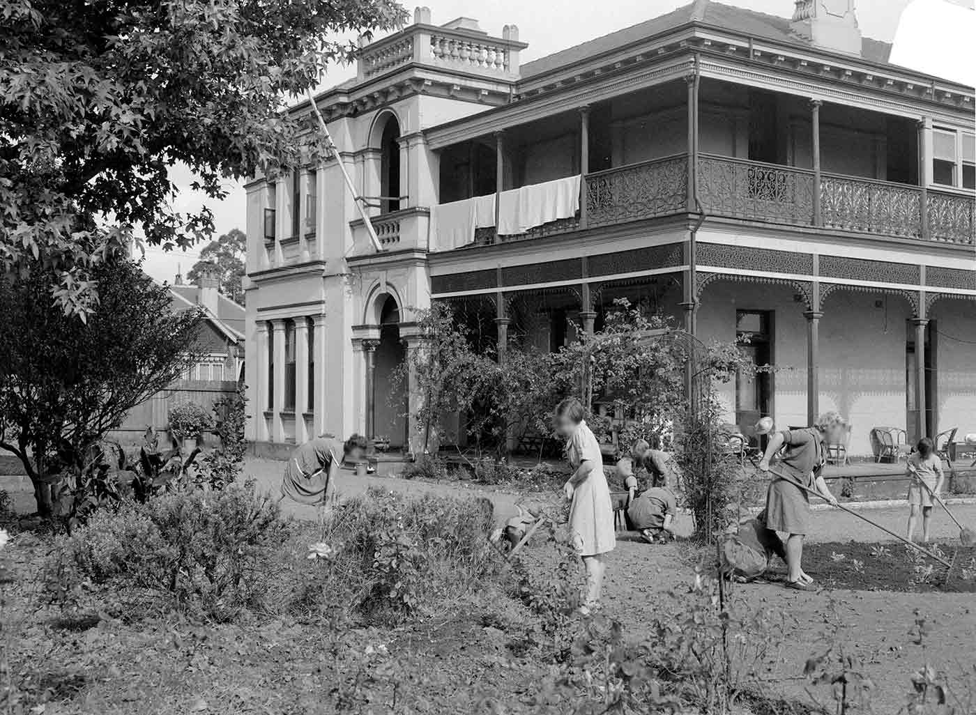 Black and white photo of a group of teenage girls at work in a garden outside a two-storey home. The girls use various tools to tend vegetable and ornamental garden beds. - click to view larger image