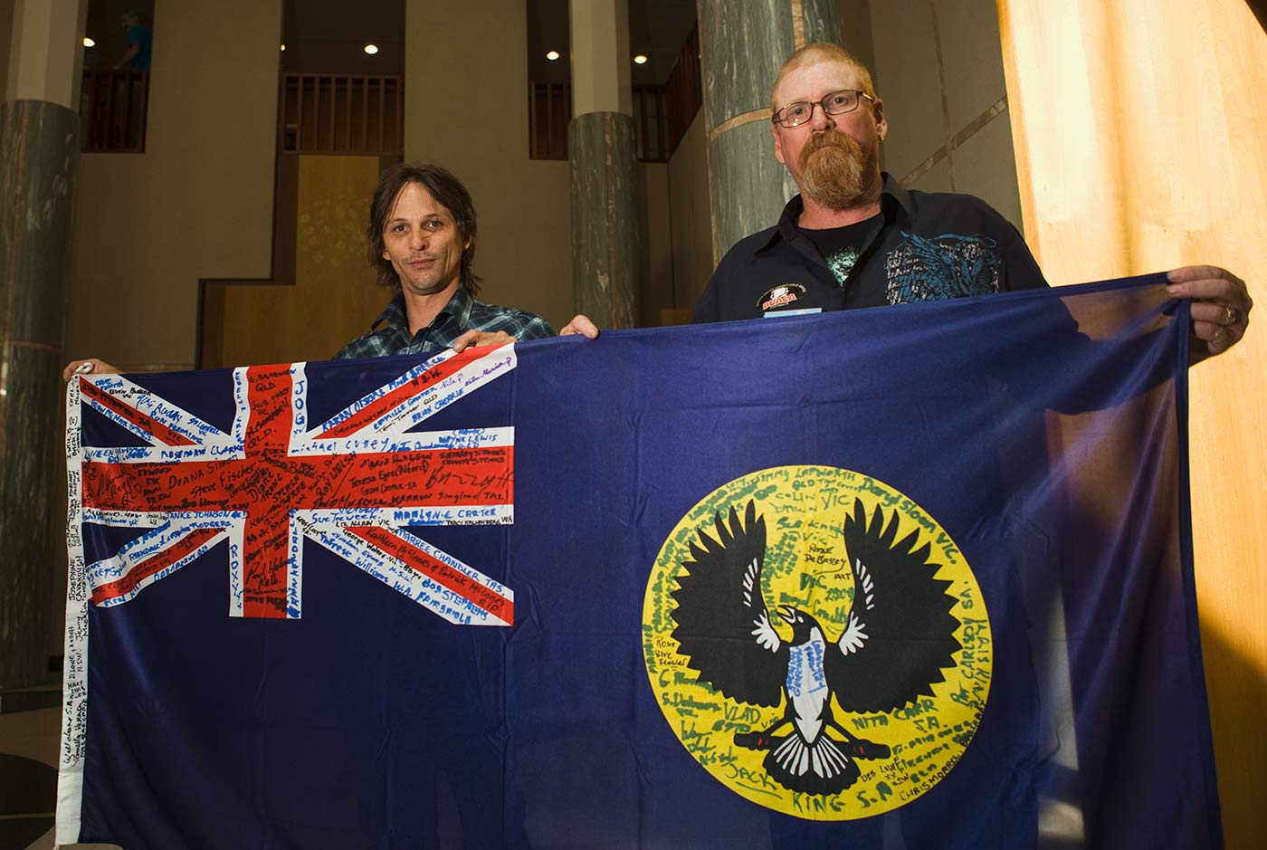 Colour photograph showing two men, standing behind a royal blue flag with ensign and insignia, covered in signatures. - click to view larger image