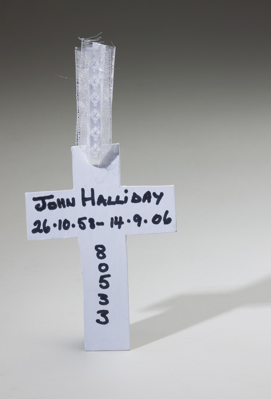 A photograph of a hand-made crucifix of white cardboard. Handwritten horizontally in black ink is 'John Halliday, 26.10.53-14.9.06'. The number '80533' is written vertically underneath. Attached to the top of the cross is a small piece of white ribbon. - click to view larger image