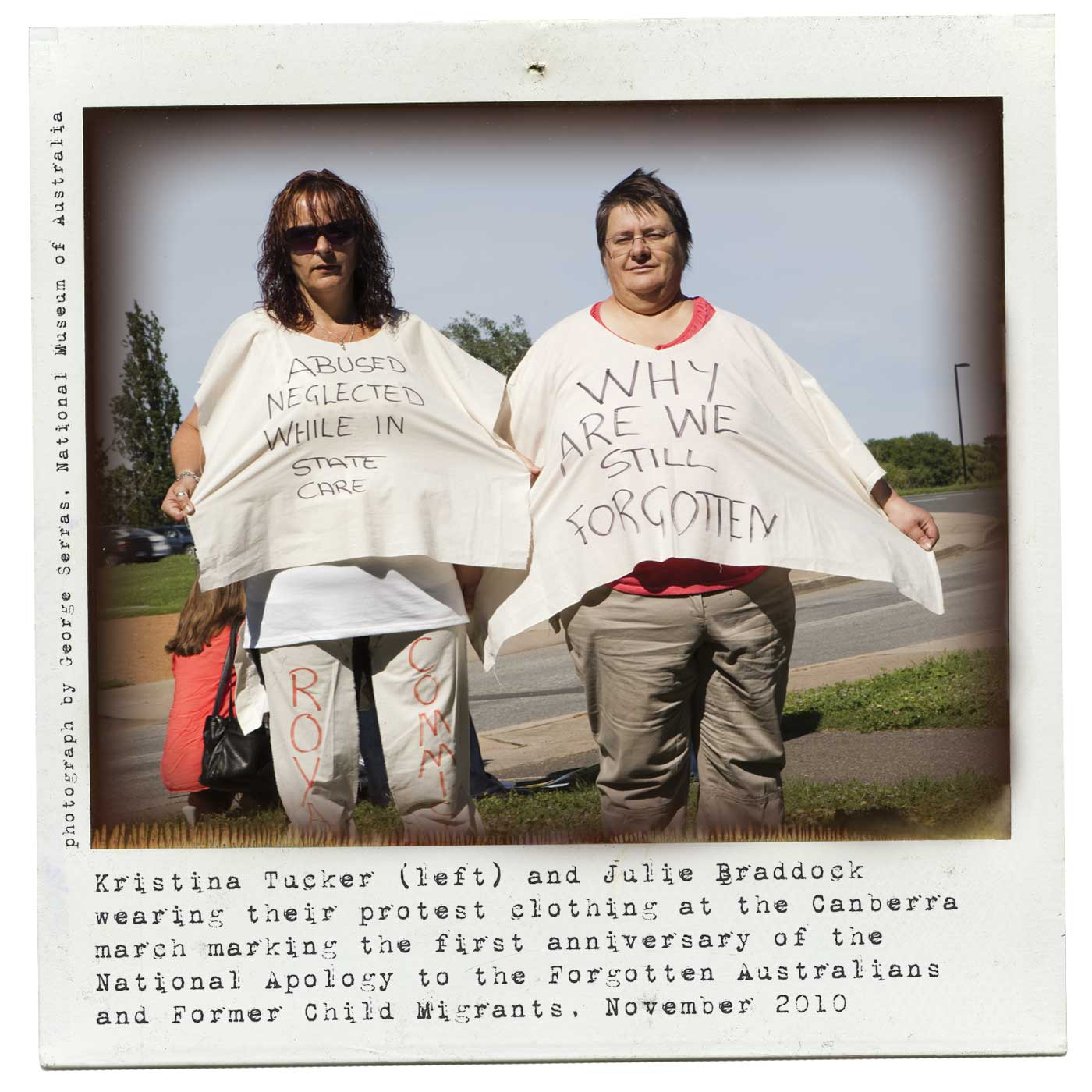 A colour Polaroid photograph showing two women holding out white shirts with protest slogans written in black felt pen. The woman on the right's shirt reads 'ABUSED NEGLECTED WHILE IN STATE CARE' and the words 'ROYAL COMMISSION' are partially visible on her trousers. The woman on the right's shirt reads 'WHY ARE WE STILL FORGOTTEN'. Typewritten text under the photos reads: 'Kristina Tucker (left) and Julie Braddock wearing their protest clothing at the Canberra march marking the first anniversary of the National Apology to the Forgotten Australians and Former Child Migrants, November 2010'. 'photograph by George Serras, National Museum of Australia' is printed on the left.