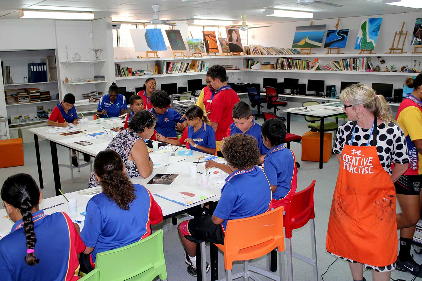 Primary school students sit at desks working on paintings while a woman, standing, talks with them. - click to view larger image