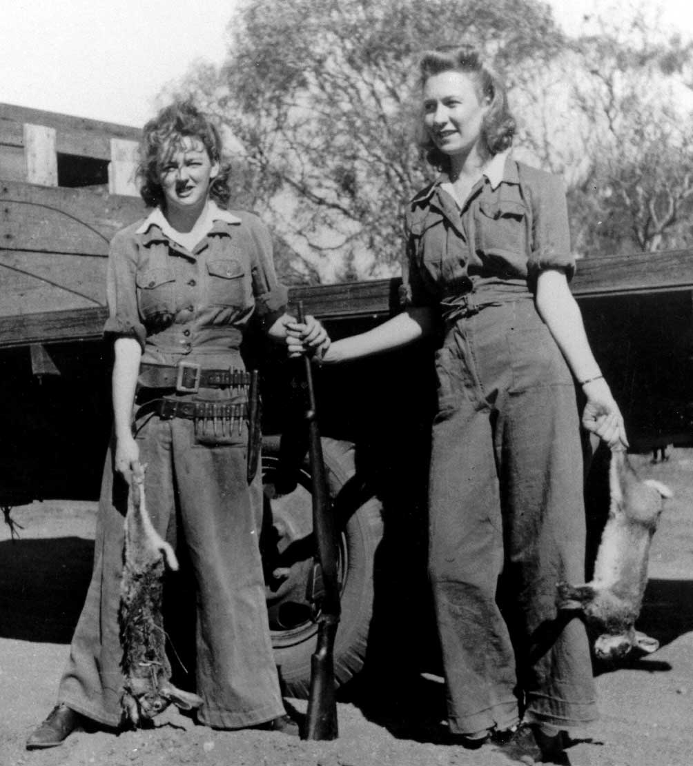 Black and white photo showing two women standing beside the tray of a truck. Both hold a dead rabbit by the hind legs and rest their hands on a rifle at centre. - click to view larger image