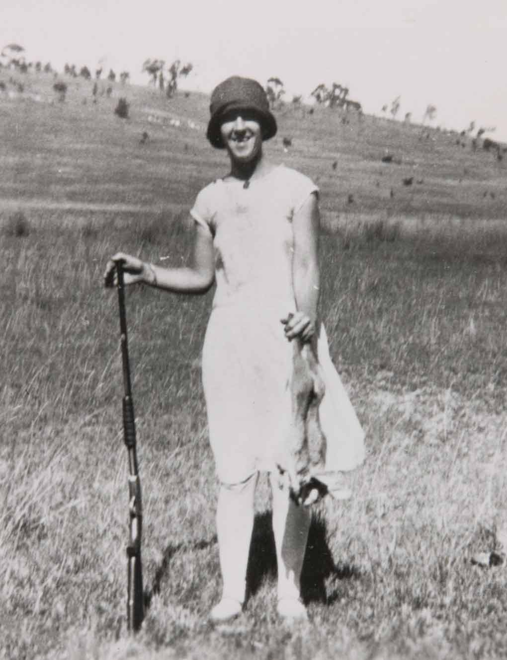 Photograph of a lady at Bathurst NSW in the 1920s with a gun in her right hand and holding a dead rabbit in her left - click to view larger image