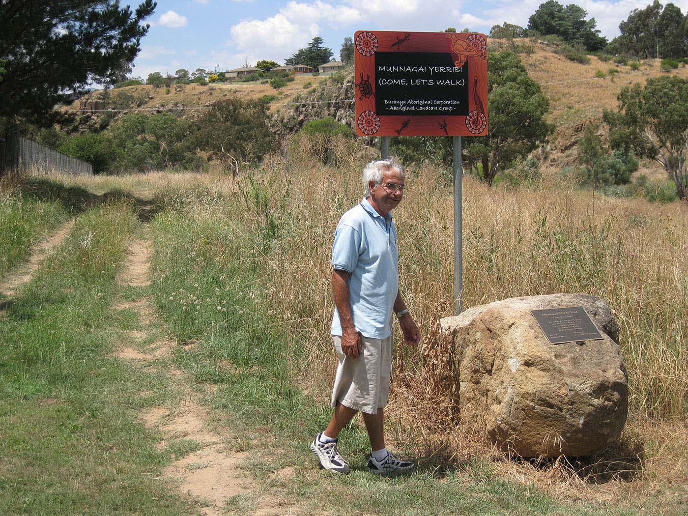 Eric Bell standing beside a dirt track, with a hill rising in the background. He is standing next to large rock with a commemorative plaque and a sign that reads 'MUNNAGAI YERRIBI (COME, LET'S WALK). Buranya Aboriginal Corporation - Aboriginal Landcare Group -'