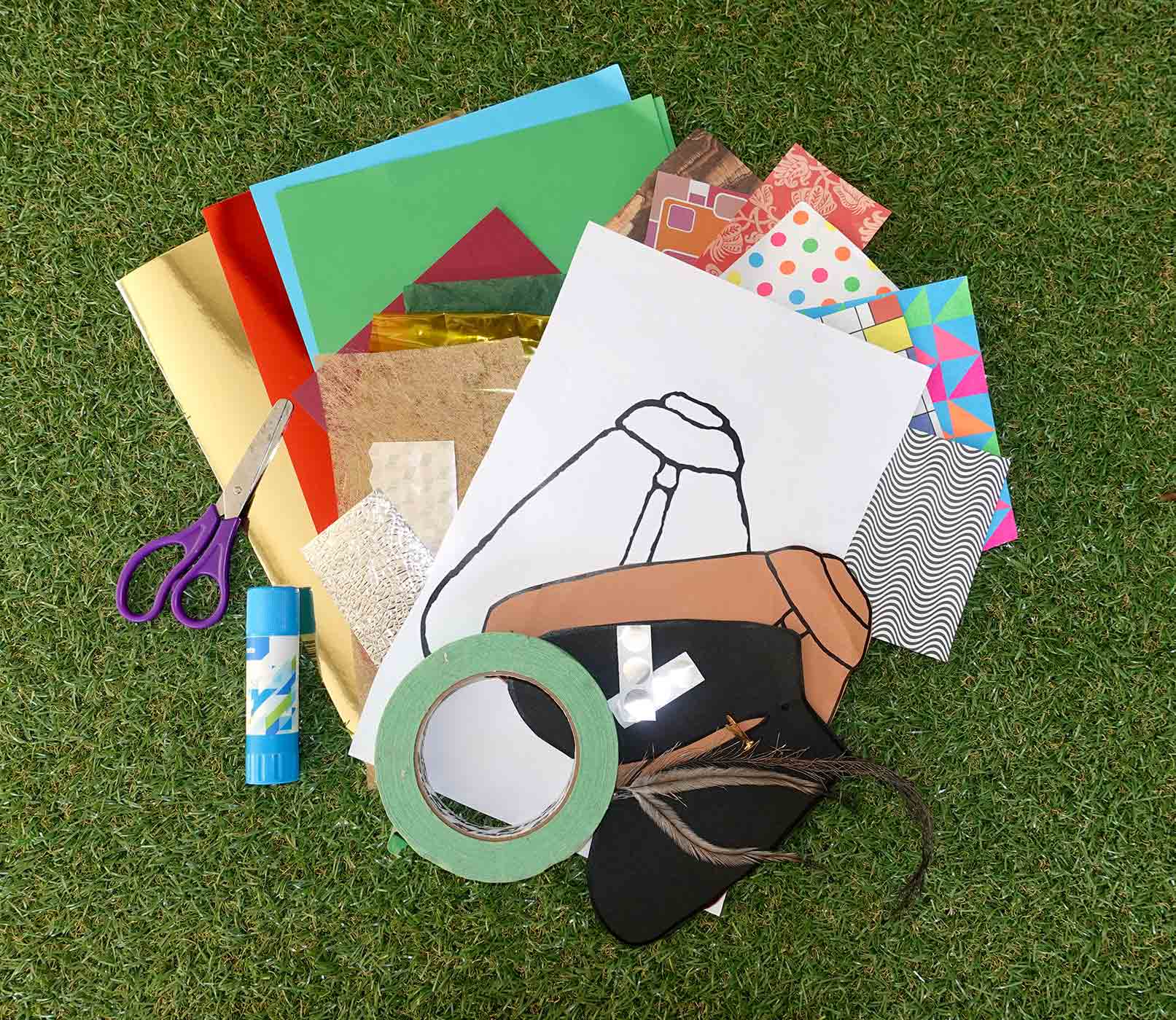 Colour photo of various materials including a paper moth template, scissors, glue, tape, feathers and other materials.