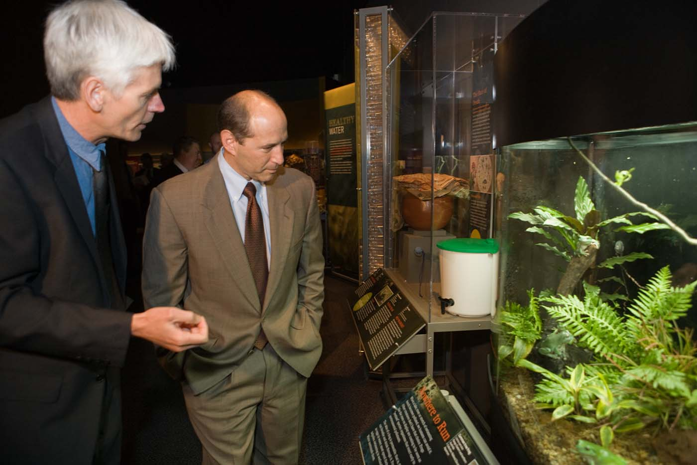 A colour photograph of Matthew Higgins (left) and Ambassador Bleich viewing one of the displays in the Water exhibition. - click to view larger image