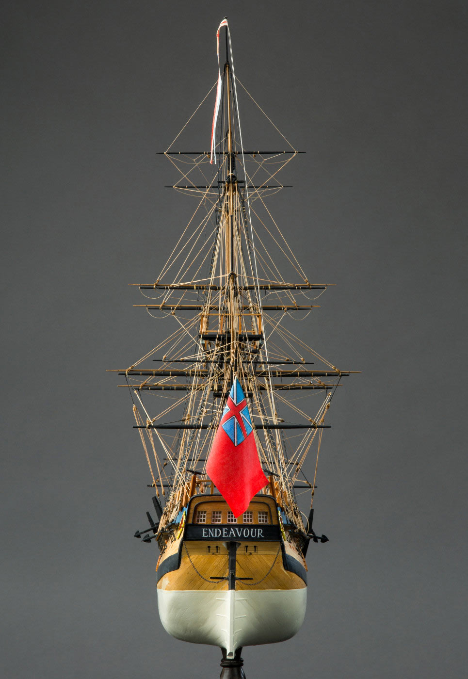 Rear view of a high-masted model wooden sailing ship, showing a red flag flying over the rear. - click to view larger image