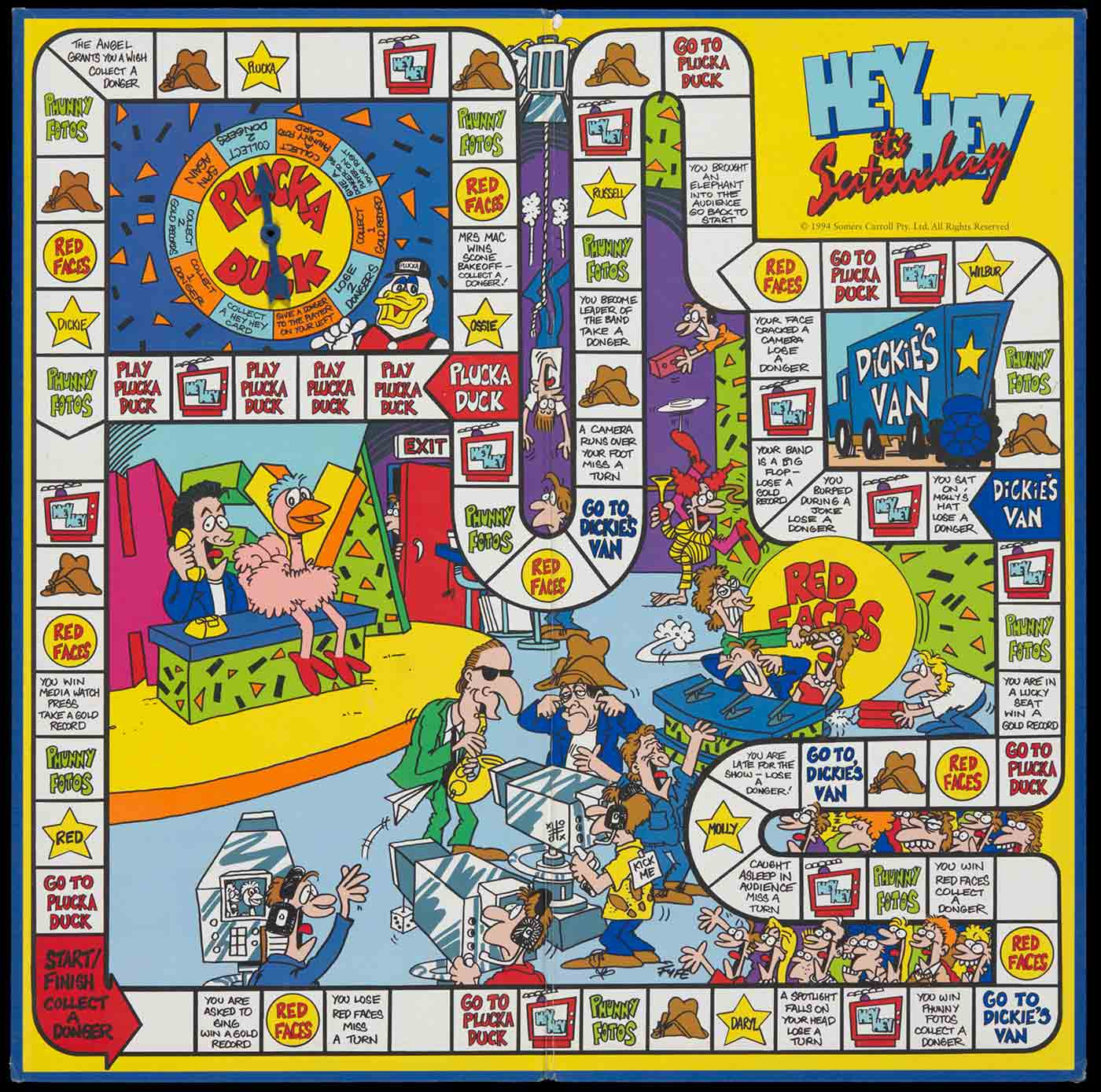 A game board with blue paper exterior and game surface interior, inscribed 'HEY HEY it's Saturday'. The interior shows white game spaces, text and illustrations in colour. A blue plastic arrow is affixed to the board in the upper left quadrant. - click to view larger image