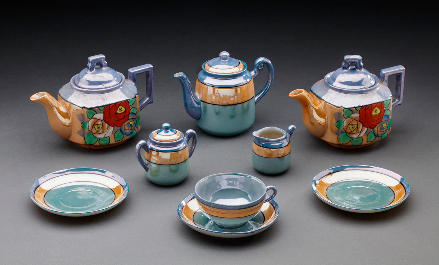 Display featuring a ceramic tea set including three teapots, a sugar basin, a milk jug, a teacup and three teacup saucers. - click to view larger image