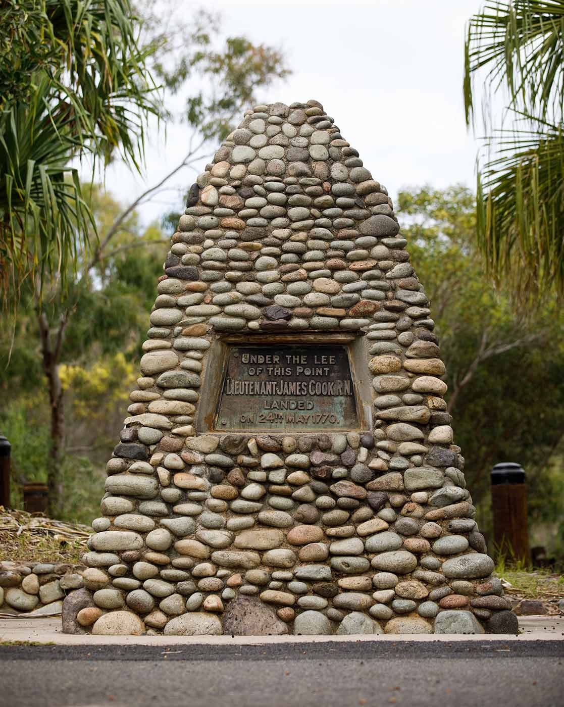 """Colour photo of a stone memorial with a plaque set in the stone that reads """"UNDER THE LEE OF THIS POINT. LIEUTENANT JAMES COOK, R.N. LANDED ON 24TH OF MAY 1770."""" - click to view larger image"""