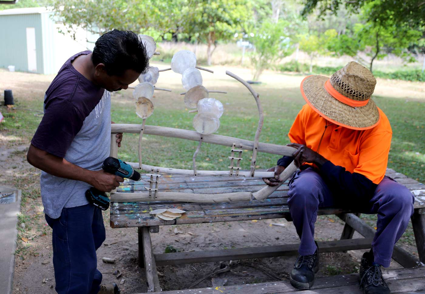 Two men work on a large sculpture made from driftwood, shellfish and other materials. - click to view larger image