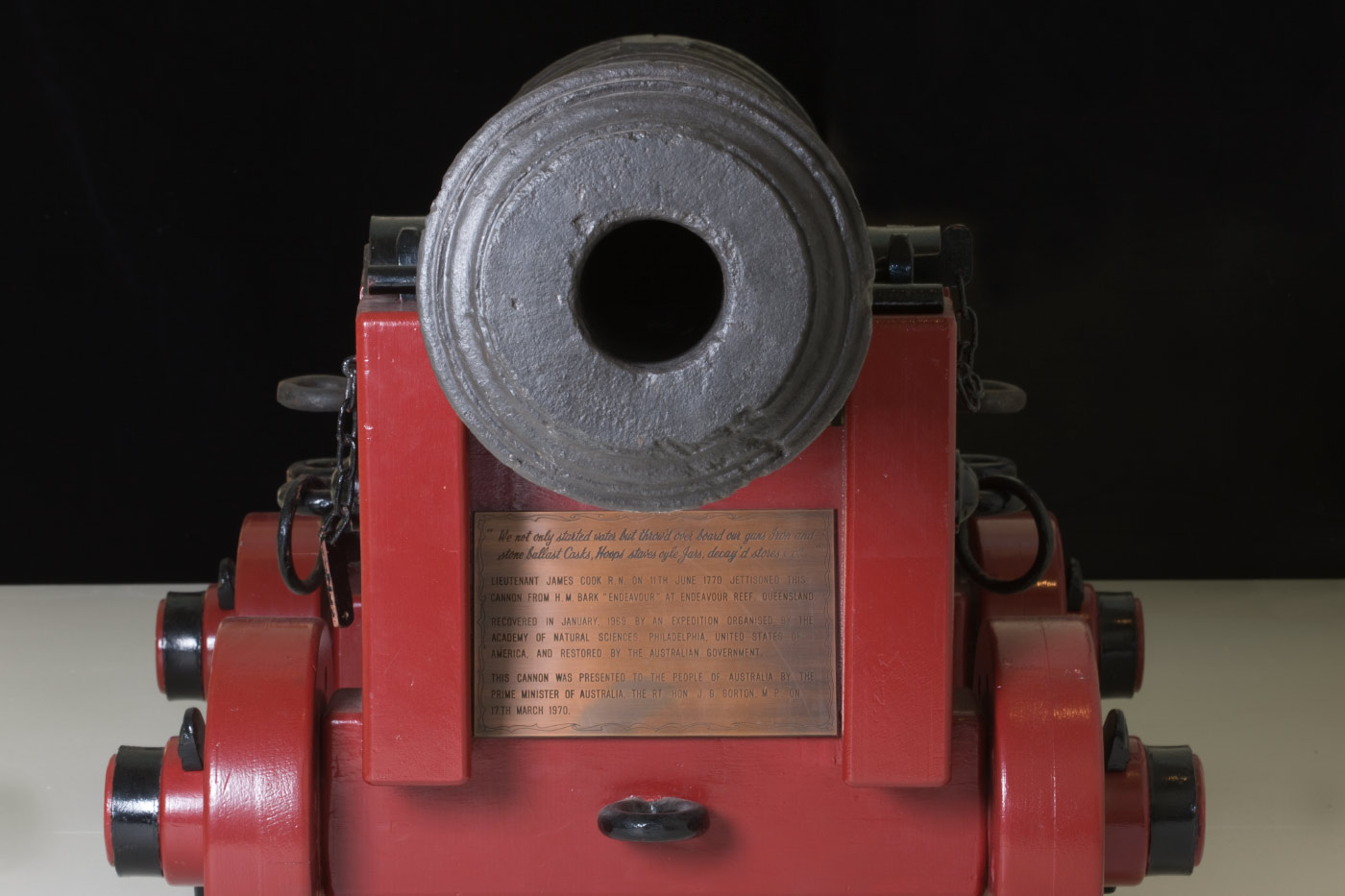 Colour photo of a cast-iron cannon mounted on a red base on wheels. A small, bronze plaque is mounted on the base under the cannon. - click to view larger image
