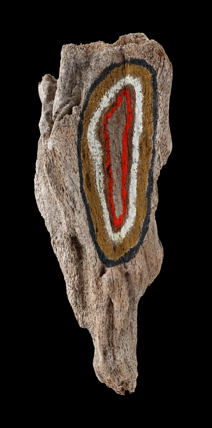 An acrylic painting on driftwood featuring a green, red, white and black concentric oval like shape on one surface of the wood. - click to view larger image