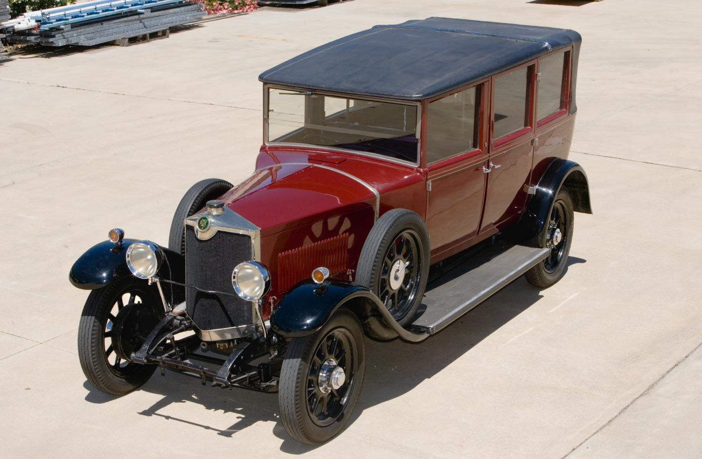 Elevated view of a polished maroon vehicle, with black trim and black leather roof. The car has running boards and mudguards.