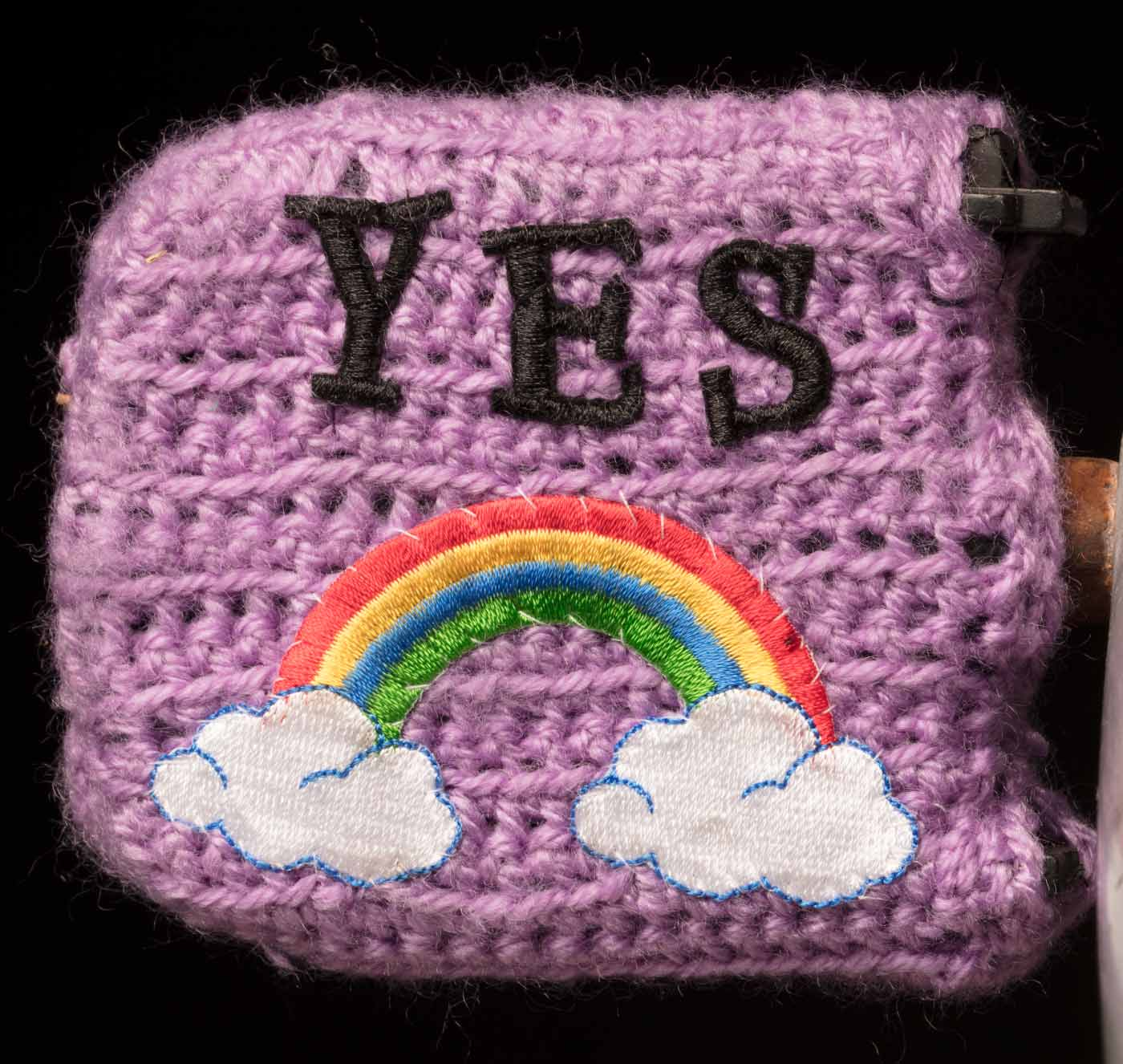 Studio photo of richly decorated pushbike pedal with the word 'YES' embroidered above an embroidered rainbow motif. - click to view larger image