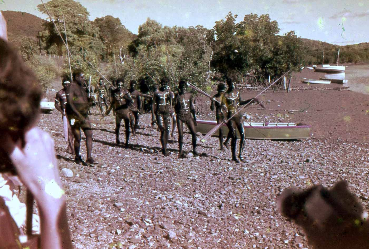 Colour photo of a group of men in costume and body paint carrying spears. They are walking along a rocky beach. - click to view larger image