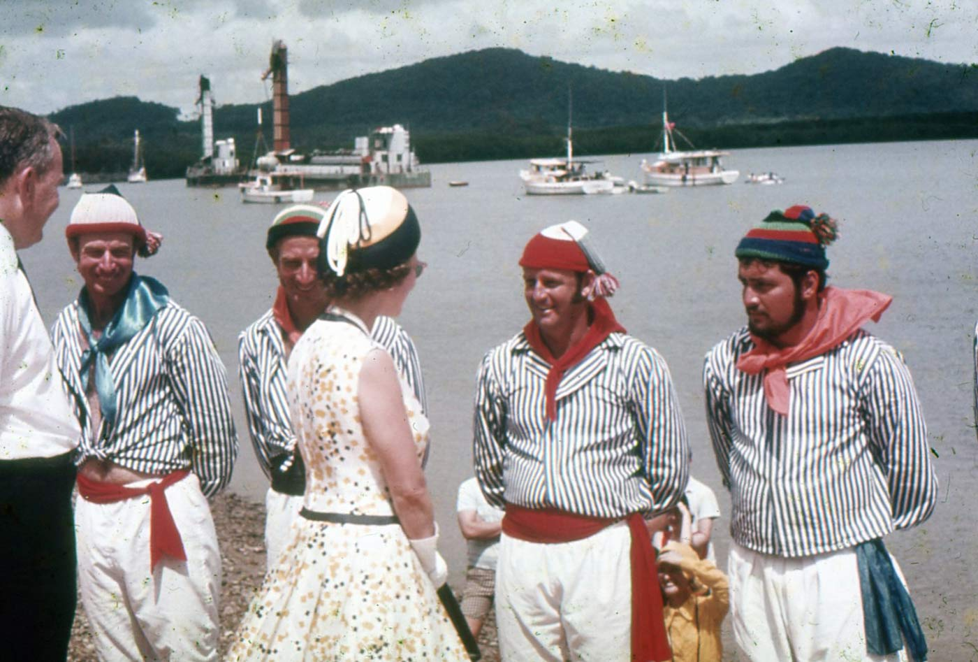 Colour photo of Queen Elizabeth II being greeted by town residents in period costume. - click to view larger image