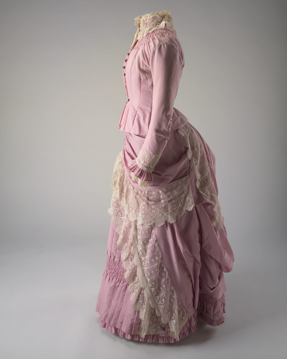 Side view of a two piece pink full length wool dress (bodice and skirt) with cream lace trimming. - click to view larger image