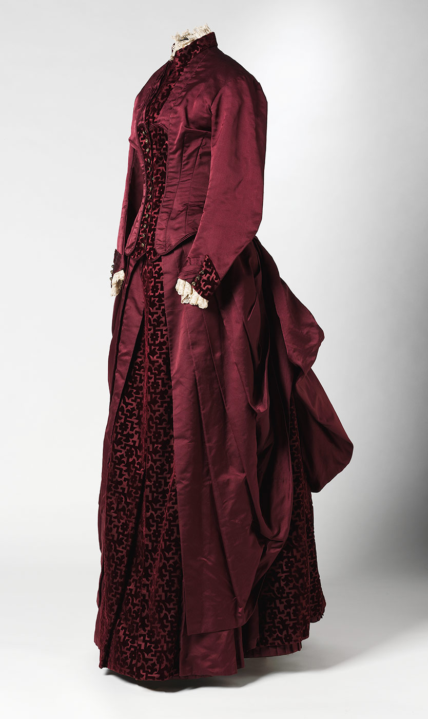 Two-piece full-length dress consisting of a bodice and skirt in burgundy duchess satin with inserts of cut velvet in a geometric and floral pattern. - click to view larger image