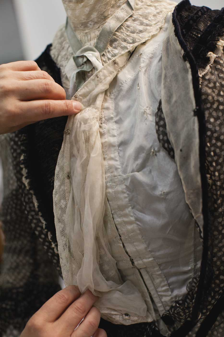A conservator adjusts the front of a dress. - click to view larger image