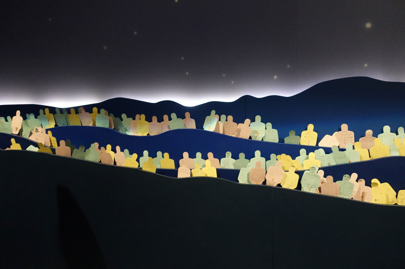 Exhibition display featuring multiple pieces of coloured paper cut out in the shape of people with hand written messages. They are positioned amongst a stylised landscape of mountains and a star-lit sky. - click to view larger image